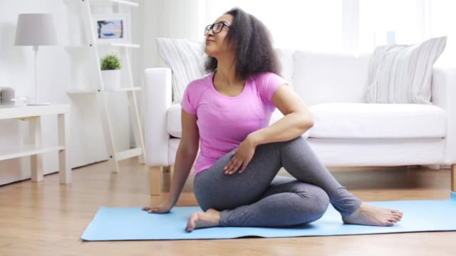 happy african woman exercising on mat at home - vídeo