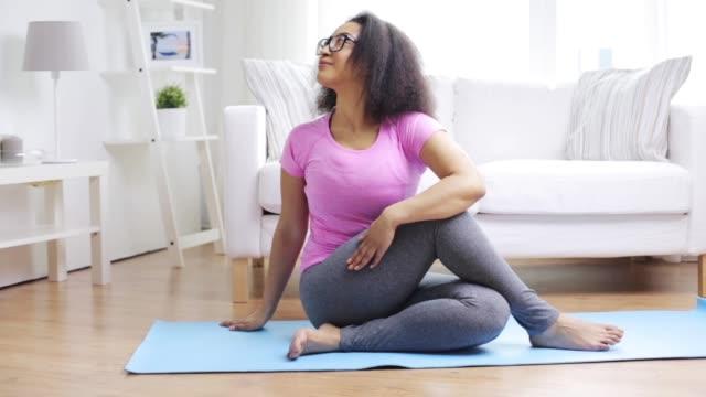 gelukkige Afrikaanse vrouw oefenen op mat thuis video