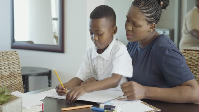 vídeos de stock e filmes b-roll de happy african woman helping her son doing homework - mãe solteira