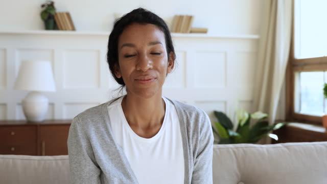 vidéos et rushes de femme africaine heureuse parlant à la webcam font l'appel vidéo à la maison - appel vidéo