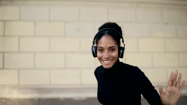 vídeos de stock e filmes b-roll de happy african woman wear wireless headphones listening to music outdoors on an empty street, relaxing after work, funny funky mixed race girl feel stress free relief, funny dancing. looking to the camera - afro americano