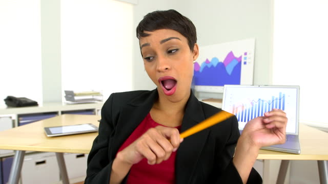 Happy AfricanAmerican businesswoman dancing and drumming with pencils at desk video