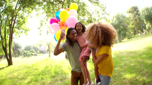 Happy African-American family spending quality time in a sunny park. video