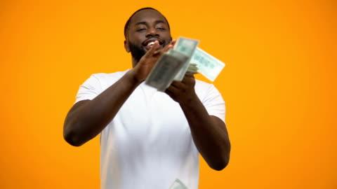 mutlu bir afrikalı-amerikalı adam fırlatma dolarlık banknotlar, para harcıyorsun, kavram - money stok videoları ve detay görüntü çekimi