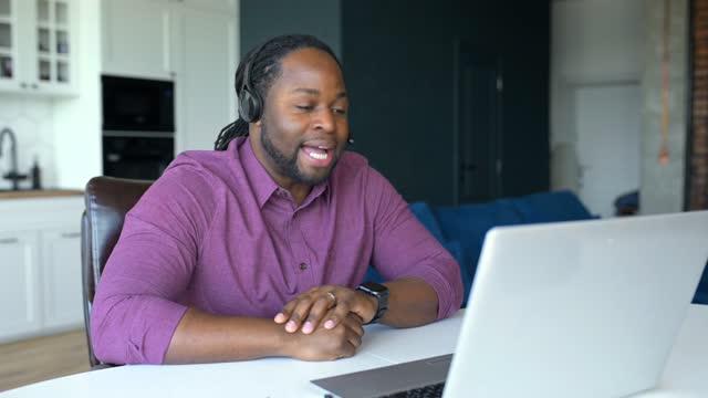 stockvideo's en b-roll-footage met gelukkige afrikaans-amerikaanse mens met slotenhaar dat draadloze hoofdtelefoonzitting thuis draagt - afro amerikaanse etniciteit