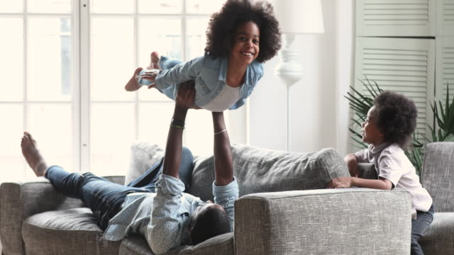 Happy afro american father and kids playing in living room