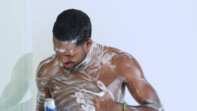 vídeos y material grabado en eventos de stock de feliz afro étnico tipo cantando canción mientras se ducha en el baño. - ducha