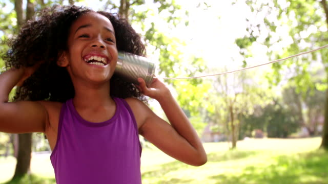 Happy Afro girl listening carefully to a tin can phone video