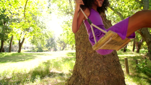 Happy Afro girl swinging under sunlit tree slow motion video