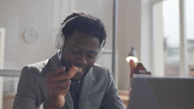 Happy Afro-American Businessman in Headphones Listening to Music at Work