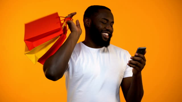 쇼핑백 및 스마트폰, 온라인 구매를 들고 행복 한 아프리카계 미국 흑인 남자 - black friday 스톡 비디오 및 b-롤 화면