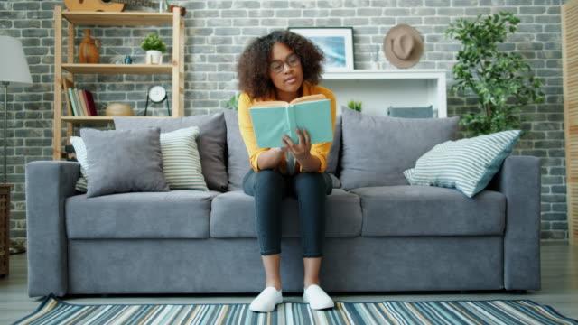 stockvideo's en b-roll-footage met gelukkig afro-amerikaanse student lezing boek en glimlachend ontspannen op de bank thuis - literatuur