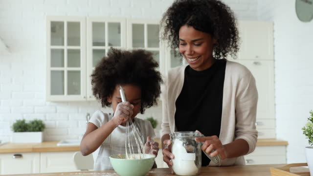 Happy afro-american young mum and cute child daughter whisking dough