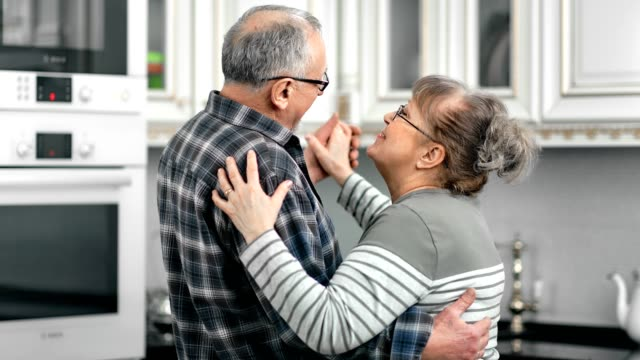 Happy aged couple having fun hugging dancing feeling love at kitchen