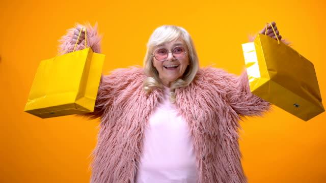 해피 에이징 레이디 노란색 쇼핑백을 보여주는 재미 있는 핑크 코트에 돈을 낭비 - black friday 스톡 비디오 및 b-롤 화면
