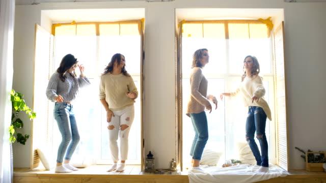 Happy and beautiful girlfriends dance on window having fun and joy in bedroom video