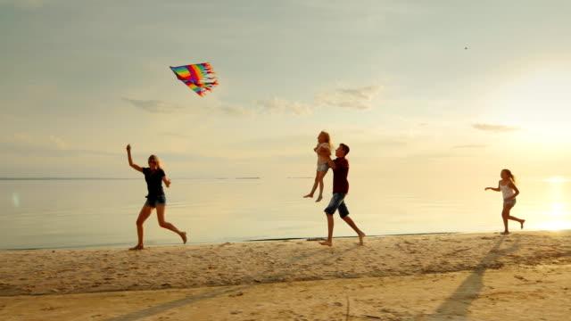Infância feliz e despreocupada. Crianças brincando com a pipa mais velha, correndo pela areia, rindo - vídeo