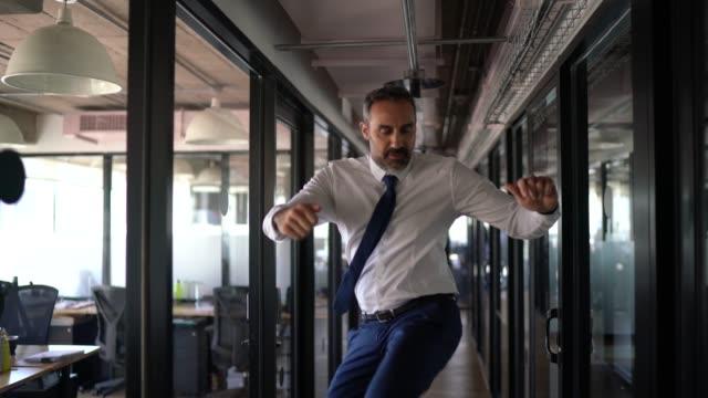 glad och trygg affärsman dansar på kontoret - gladlynt bildbanksvideor och videomaterial från bakom kulisserna