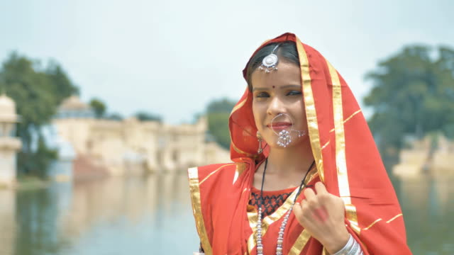 A happy and conservative girl in traditional attire and jewelry smiling in Indian countryside