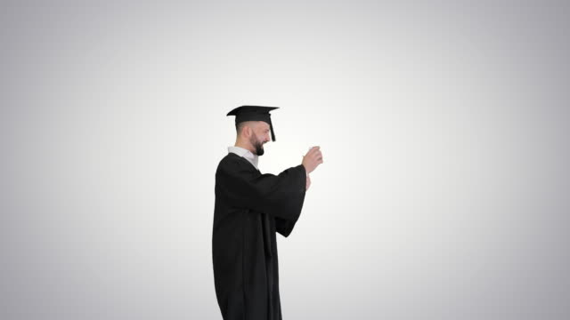 Happy and excited graduate male student throws hat in the air on gradient background