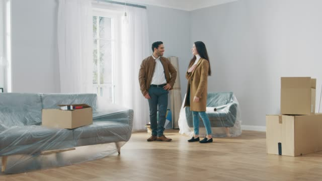 Happy and Excited Young Couple Look Around In Wonder at their Newly Purchased / Rented Apartment. Beautiful People Happily Embracing. Big Bright Modern Home with Cardboard Boxes Ready to Unpack. Happy and Excited Young Couple Look Around In Wonder at their Newly Purchased / Rented Apartment. Beautiful People Happily Embracing. Big Bright Modern Home with Cardboard Boxes Ready to Unpack. Shot on RED EPIC-W 8K Helium Cinema Camera. home ownership stock videos & royalty-free footage