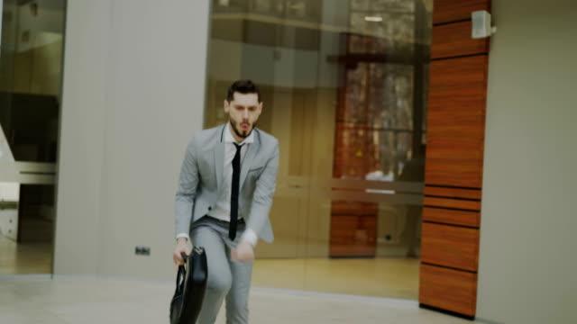 happy and funny businessman with briefcase dancing in office lobby while nobody watching him - młodzi mężczyźni filmów i materiałów b-roll