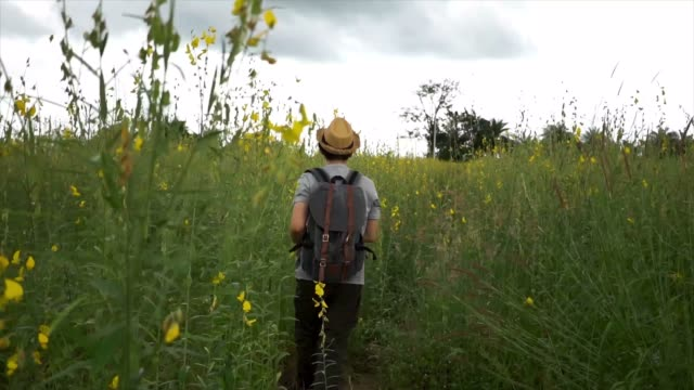 Happy and joyful male tourist backpacker with hat and bag excitedly walking and jumping on the countryside grassland