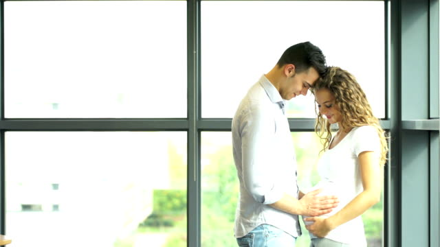 Happy and young pregnant couple in park in summer video