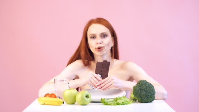 Happy anorexic girl greedily eats chocolate. Violation of diet. Poor diet. Anorexia.