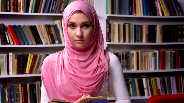 happy arab female in pink hijab is standing in library and smiling cheerful, middle east mood, quiet place - abbigliamento religioso video stock e b–roll