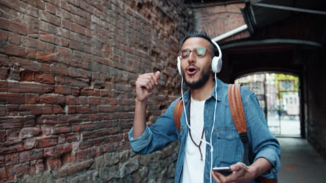 Happy Arab tourist in headphones listening to music singing dancing outdoors Happy Arab tourist in headphones listening to music singing dancing outdoors having fun alone in the street holding smartphone. Youth culture and devices concept. hipster stock videos & royalty-free footage