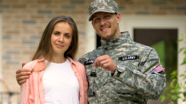 happy army veteran hugging wife holding house key standing outside cottage - key ring stock videos & royalty-free footage