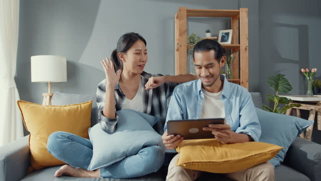 Happy asia young attractive couple sit on couch use tablet shopping online furniture decorate home in the living room at new house. Happy asia young attractive couple man and woman sit on couch use tablet shopping online furniture decorate home in the living room at new house. Young married moving home shopper online concept. financial planning stock videos & royalty-free footage