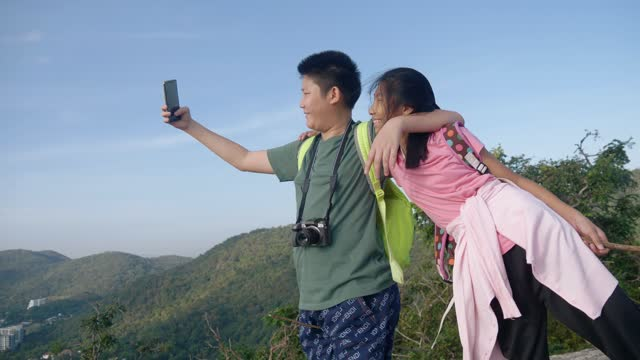 Happy Asian backpacker children selfie themselves together on the top of Mountain View, lifestyle concept.