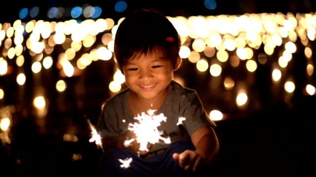 slo mo 행복 아시아 소년 첫 번째 지주 폭죽 손에 - 촛불 조명 장비 스톡 비디오 및 b-롤 화면