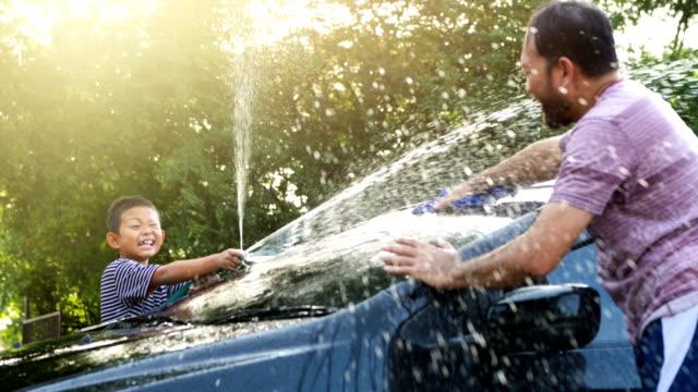 vidéos et rushes de heureux garçon asiatique aider parent lavage voiture sur l'eau éclaboussant avec la lumière du soleil à la maison, le mouvement lent. vacances actives en famille. - laver