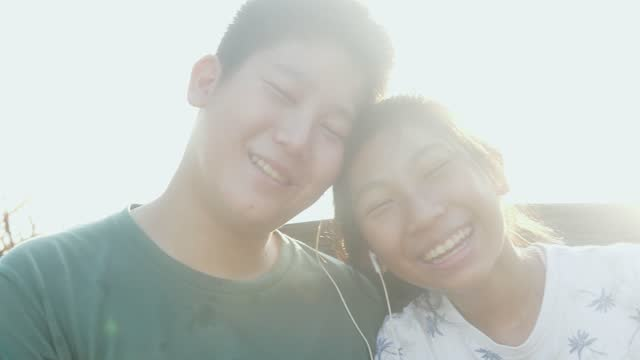 Happy Asian boy sharing earplugs for his sister and listening songs together with sunlights background, technology concept.