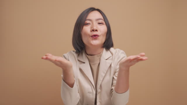 happy asiatiska affärskvinna i kärlek skicka luft kyss och titta på kameran isolerade över beige bakgrund. 4k-video - blåsa en kyss bildbanksvideor och videomaterial från bakom kulisserna