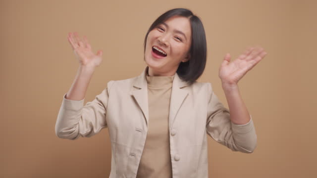 Happy asian business woman waving her hand for greeting and looking at camera isolated over beige background. 4K video