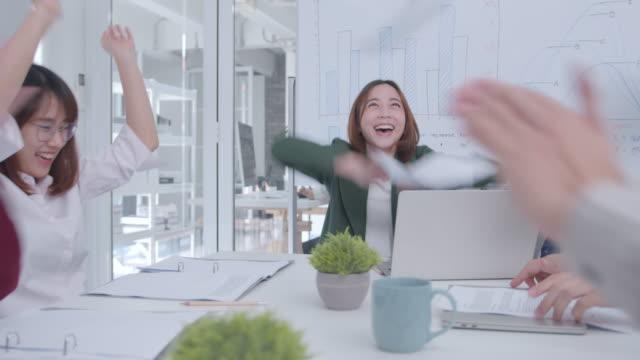 felice uomo d'affari asiatico e donna d'affari che lancia documenti di scartoffie battendo mano, stretta di mano dopo aver ricevuto buone novità. - arto umano video stock e b–roll