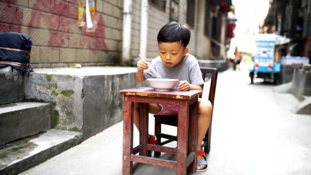 Glücklich asiatische Kind Essen köstlichen Nudeln mit chopstick – Video