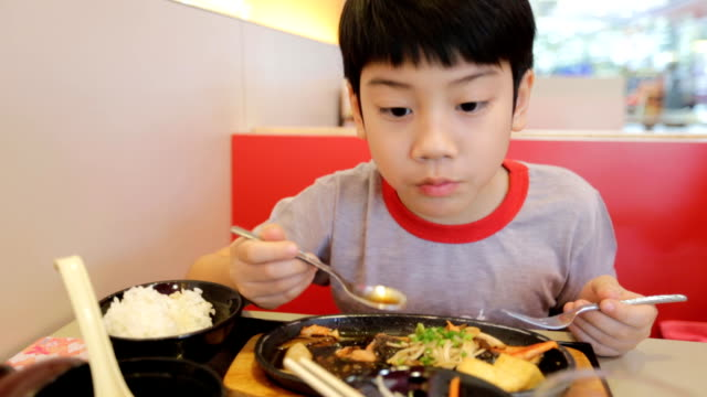Happy asian child eating sushi in a restaurant video