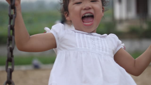 happy asian child enjoying swing with her mother,DOF,loopable video