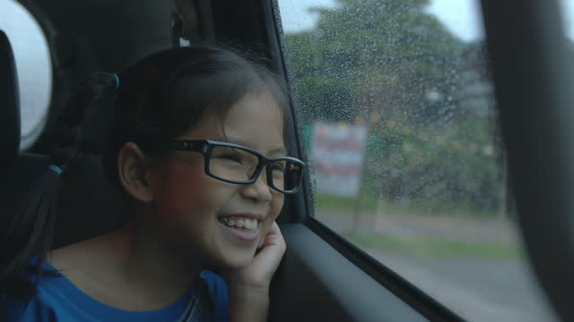 Happy asian child girl is looking out from car window and sing a song
