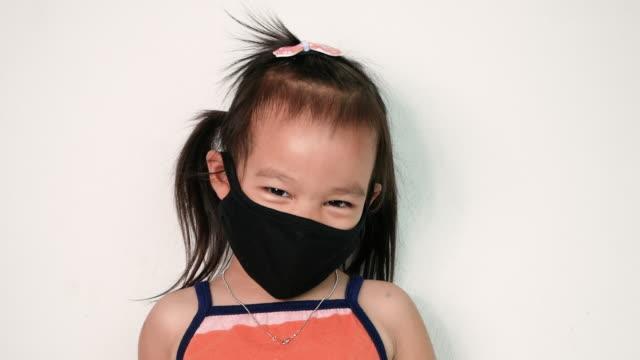 glad asiatisk barn flicka bär ansiktsmask för skydd mot luftföroreningar eller virusepidemi på vit bakgrund. hälso- och sjukvårdskoncept. - face mask bildbanksvideor och videomaterial från bakom kulisserna