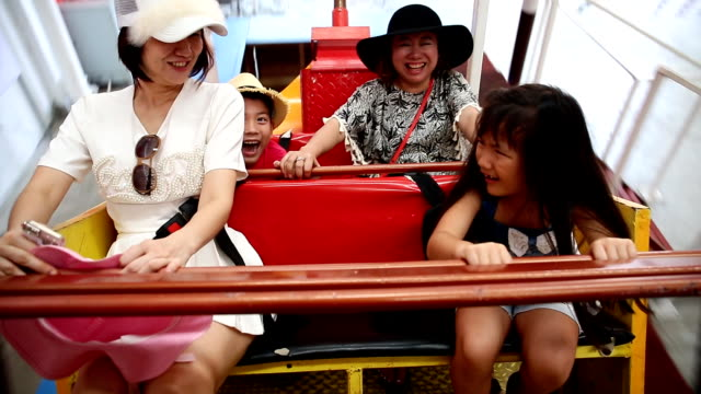 Happy Asian child with mother playing speed boat video