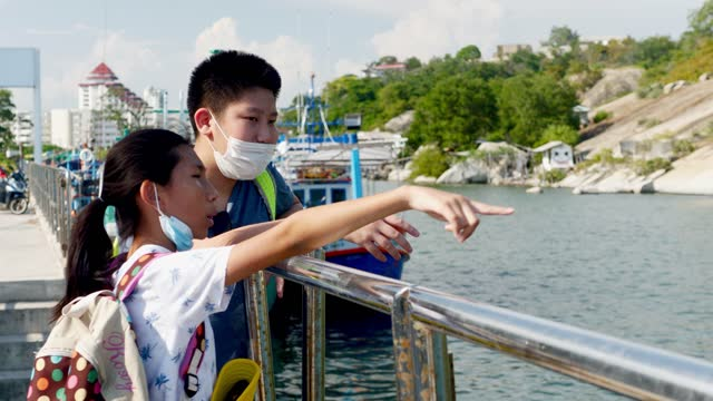 Happy Asian children wearing face mask enjoying on the fishing pier together in sunny day, lifestyle concept.