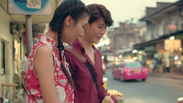 lyckliga asiatiska paret att köpa snabbmat i kinesiska nyåret festival på bangkok. - thailändsk kultur bildbanksvideor och videomaterial från bakom kulisserna