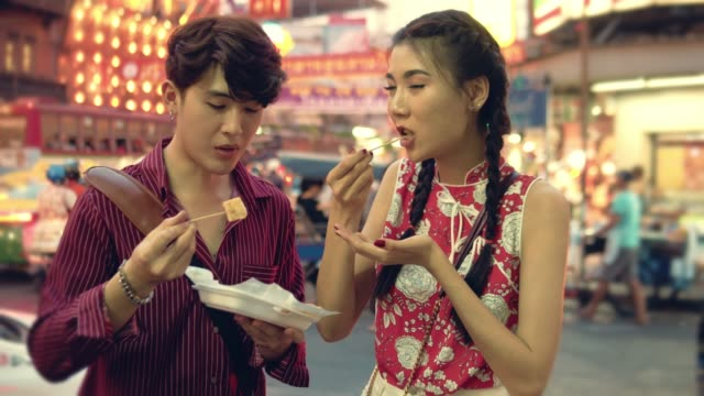 happy asian couple eating street food in chinese new year festival at bangkok. - ночной рынок стоковые видео и кадры b-roll