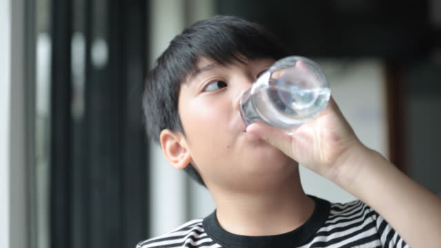 Happy asian cute boy drinks water from a bottle . video